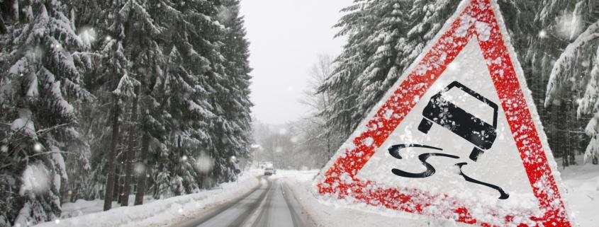 Auf einer verschneiten Straße befinden sich rechts und links verschneite Tannen und im Vordergrund ein Warnschild für Rutschgefahr